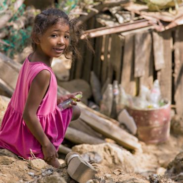 """Taken on-site with an NGO in Puerto Colombia near Barranquilla in Colombia. I was with an NGO that specializes in constructing """"emergency homes"""" for those most in need, in poverty stricken areas. This young girl briefly passed the site we were working on to make her way down to the wooden slum below. I identified the shot from a distance and ran swiftly but calmy so as to not alarm the girl, I got her attention for all of about 2 seconds to compose and photograph her. No room for errors, this was the only photograph I managed to get of her before she continued making her way down the slope."""